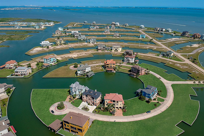 Corpus Christi, TX aerial / drone photo of a beautiful home in an ocean cul-de-sac with blue water.